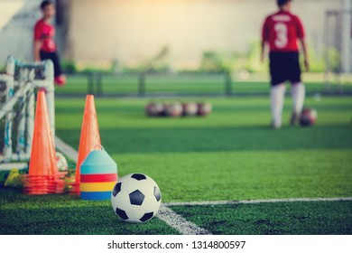 soccer ball and soccer training equipment on green artificial turf with blurry of soccer players training. Soccer Academy.