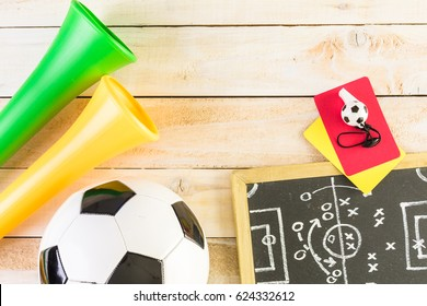 Soccer ball and Vuvuzela stadium horns on a wood background.