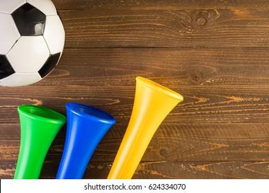 Soccer ball and Vuvuzela stadium horns on a wood background.