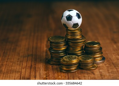 Soccer bet concept with small football on top of coin stack, making money by predicting sport results.