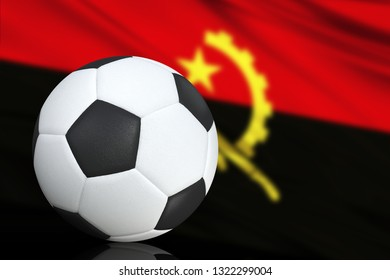 Soccer black and white ball close up, in the background a blurred flag of Angola. The image takes place for your text.