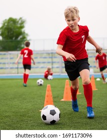 Soccer Boy on Training with Ball and Soccer Cones. Dribbling Drill. Soccer Kids Dribble Training. Youth Soccer Club Practice Session. Boys in Sports Team in Red Jersey Uniforms