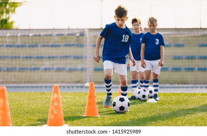 Soccer camp for kids. Boys practice dribbling in a field. Players develop good soccer dribbling skills. Children training with balls and cones. Soccer slalom drills to improve football dribbling pace