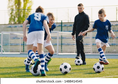 Soccer camp for kids. Boys practice football dribbling in a field. Players develop soccer dribbling skills. Children training with balls. Soccer slalom drills to improve football dribbling pace