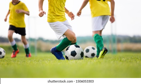 Soccer camp for kids. Boys practice dribbling in a field. Players develop good soccer dribbling skills. Children in yellow shirts training with balls. Soccer slalom drills on pitch