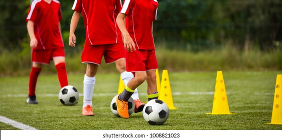 Soccer camp for kids. Children training soccer skills with balls and cones. Soccer slalom drills to improve football dribbling fast