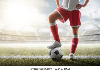 Soccer closeup. Leg of soccer player on the ball. Soccer background. Day stadium. Sport