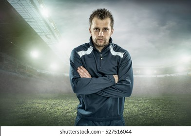 Soccer coach stay at stadium under light.