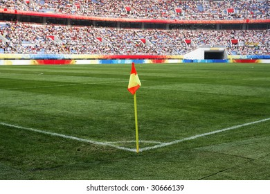 A soccer corner flag in a large stadium filled with spectators.