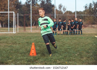 Soccer Drills: The Slalom Drill. Youth soccer practice drills. Young football player training on pitch. Soccer slalom cone drill. Boy in soccer jersey running between cones.