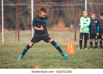 Soccer Drills: The Slalom Drill. Youth soccer practice drills. Young football player training on pitch . Soccer slalom cone drill. Boy in soccer jersey running and jumping between cones and ring.