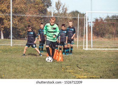 Soccer Drills: The Slalom Drill. Youth soccer practice drills. Young football player training on pitch. Soccer slalom cone drill. Boy in soccer jersey running with ball between cones.