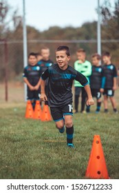Soccer Drills: The Slalom Drill. Youth soccer practice drills. Young football player training on pitch . Soccer slalom cone drill. Boy in soccer jersey running between cones and ring ladder marker.