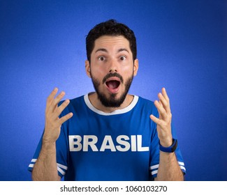 Soccer fan in action emotions: happy, amazed. Supporter of Brazil National Team of football is surprised.
