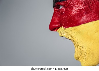 Soccer fan with german strip flag painted over face