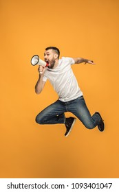 Soccer fan jumping on orange background. The young man as football fan with megaphone isolated on orange studio. Support concept. Human emotions, facial expression concepts.