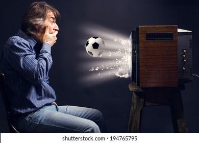 Soccer fan watching football on retro TV.