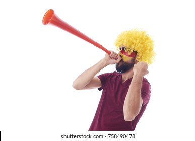 Soccer fan with wig and vuvuzela celebrating