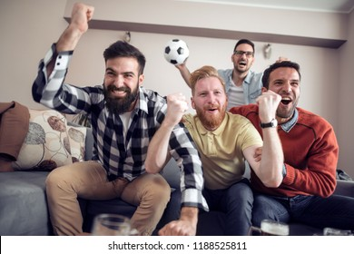 Soccer fans emotionally watching game in the living room.