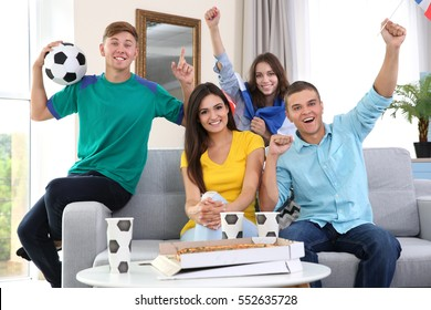 Soccer fans emotionally watching game in the room