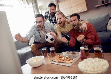 Soccer fans watching game in the living room,having fun together.