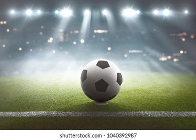 Soccer field with ball on the stadium and lights in background