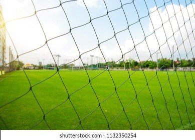 Soccer field or football field view through nylon net on clearly day.