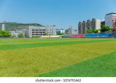 Soccer field and stands in university campus under sunlight