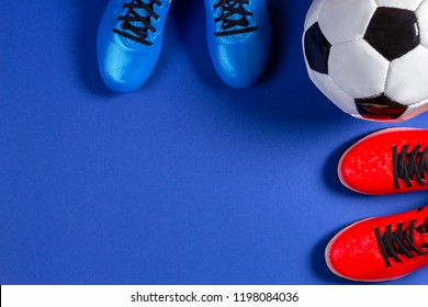 Soccer football background. Top view of soccer ball and two pair of soccer football sports shoes on blue background