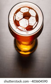 soccer or football ball symbol on foam in beer glass on black table, view from above
