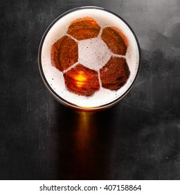 soccer or football ball symbol on foam of fresh lager beer glass on black table, view from above