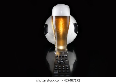 Soccer / Football and Beer. Soccer ball over glass of beer with TV remote on mirror. Dark luxury style. Design.