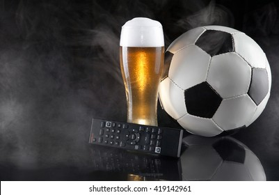 Soccer / Football and beer. Glass of beer with TV remote and soccer ball on mirror in smoke. Dark luxury style. Space for text.