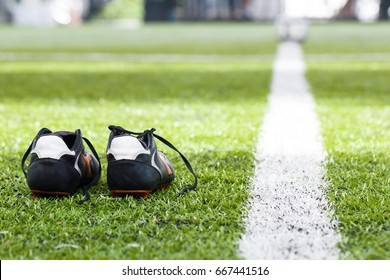 Soccer football boots are placed on green grass in the football field and have white lines to distant footballs