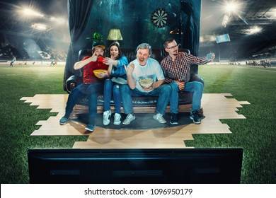 Soccer football fans sitting on sofa at home and watching TV in the middle of a football field. Football concept. Full immersion into the match. Real emotions. Live broadcast. Dynamic action. Collage