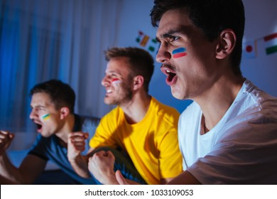 Soccer or football fans watching the match at home, cheering and celebrating goal