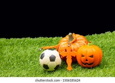 Soccer football halloween with pumpkin and Christ cross are on green grass