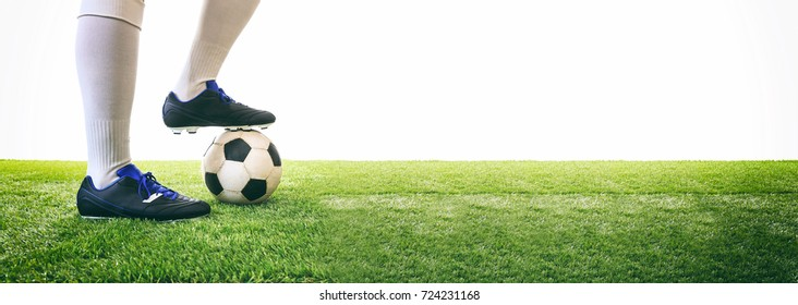 Soccer, football kick off. Man controls a soccer ball on the grass. White background and copy space