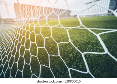 Soccer or football net background, view from behind the goal with blurred stadium and field pitch.