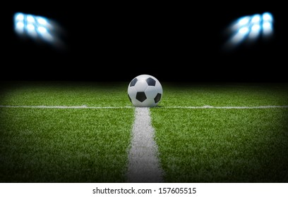 Soccer Football on the Green field with bright spotlights