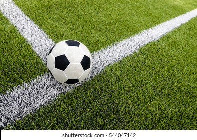 The soccer football on the white line in the artificial green grass field