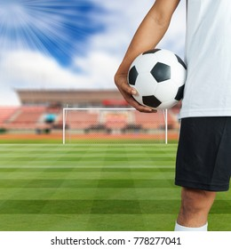 Soccer football player holding a ball in a football field