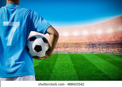 soccer football player no.7 in blue team concept holding soccer ball in the stadium