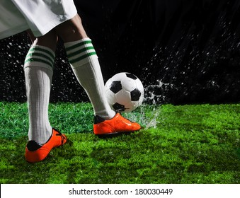 soccer football players kicking to soccer ball on green grass field with splashing of transparent water against black background