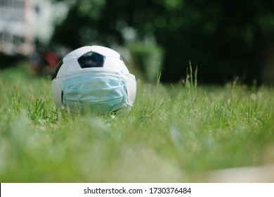 Soccer football with surgical face mask on natural turf grass, symbol image for sports during the corona covid-19 pandemic in 2020