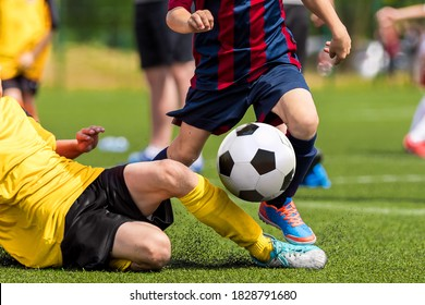 Soccer football tackle moment. Skill of tackling in soccer game. Two footballers in a duel. Running school age boys. Kids kicking soccer ball on grass pitch