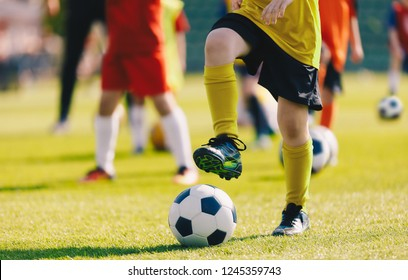 Soccer Football Training for Children. Kids Playing Soccer on Training Football Pitch. Beginner Soccer Drills for Kids. Coach in the Background Coaching Youth Soccer