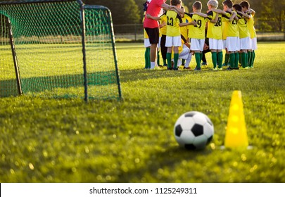 Soccer football training for young boys. Training session on the grass soccer field. Soccer ball and pylon cone and soccer goal in the foreground. Youth football team standing together with coach