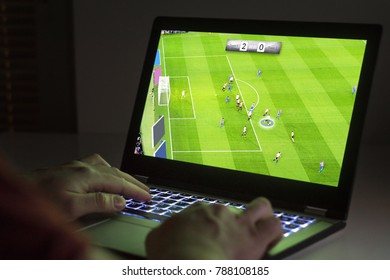 Soccer or football video game in laptop. Young man playing with computer. Online gaming and e sports concept.