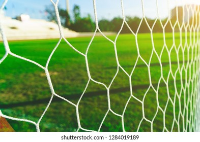 Soccer goal net with grass green, The nets of football goal with field grass, football net and blue sky.